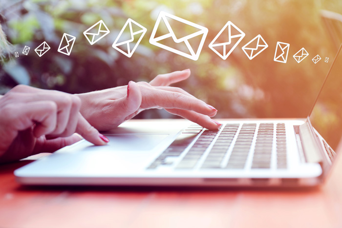 Hands typing on a laptop outdoors with envelope symbols above laptop. Email campaigns are part of corporate event planning tips.