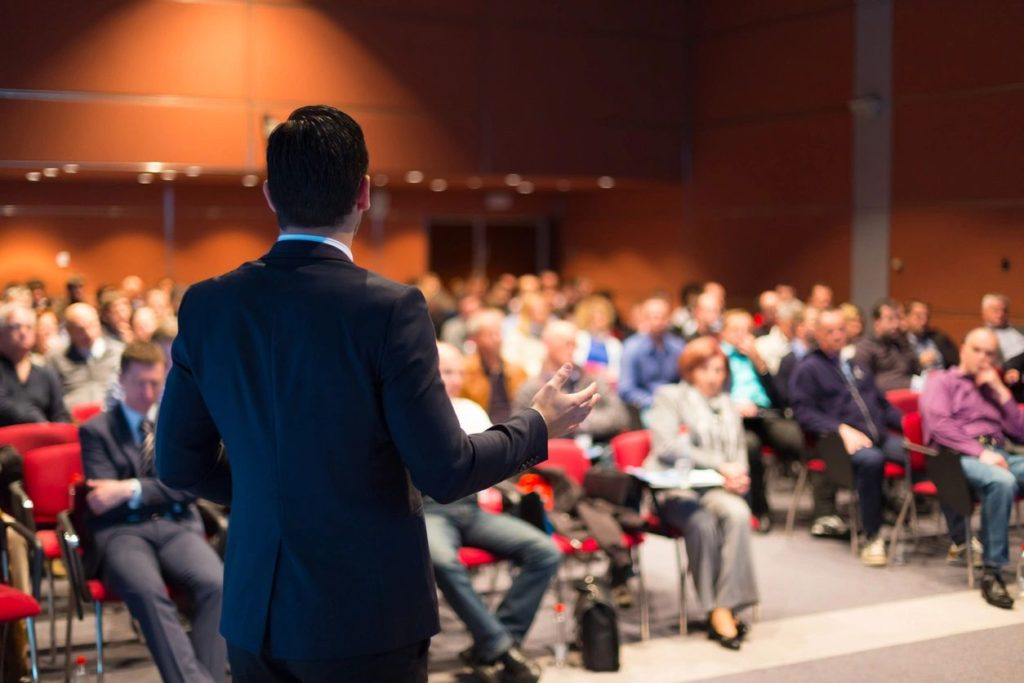 Image of back of man standing in front of a room of seated people speaking at a trade show event